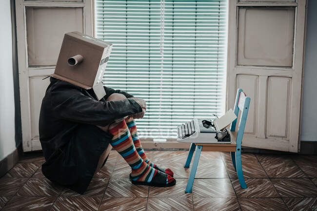 Man wearing cardboard box and striped socks sitting on floor by chair with retro typewriter — Stock Photo
