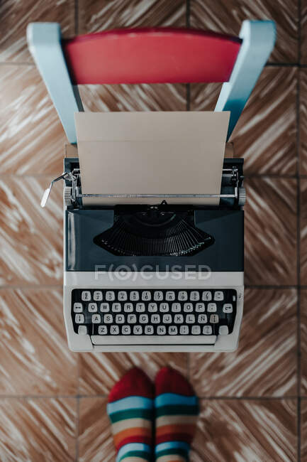 Top view of feet in stripped socks standing near old fashioned typewriter — Stock Photo