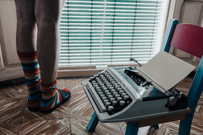 Чоловік на ногах у смугастих шкарпетках стоїть біля старомодної друкарської машинки. — стокове фото