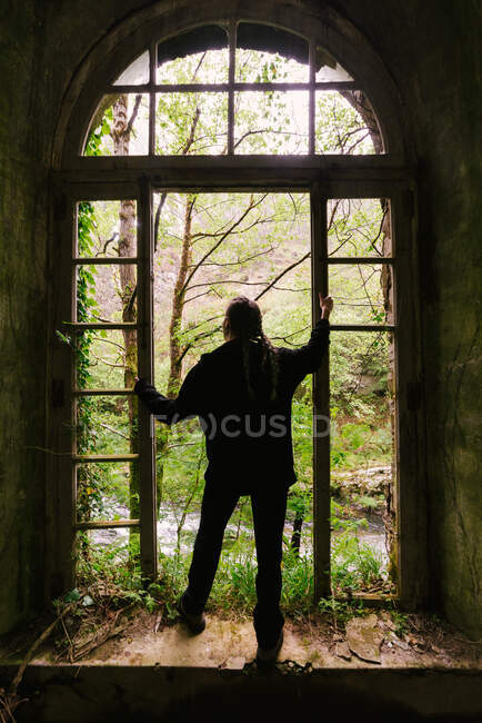 Back view of anonymous female standing near window of shabby building abandoned in forest of Hoces del Esva and admiring woodland scenery — Stock Photo