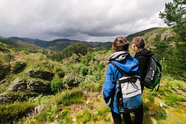 Visão traseira de caminhantes femininas irreconhecíveis em outerwear em pé na colina rochosa e admirando a vista incrível da paisagem das terras altas durante o dia ensolarado — Fotografia de Stock