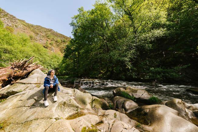 Calma turista in capispalla seduto sulla riva rocciosa e ammirare splendida vista del fiume di montagna rapido mentre si rilassa durante il trekking a Hoces del Esva — Foto stock