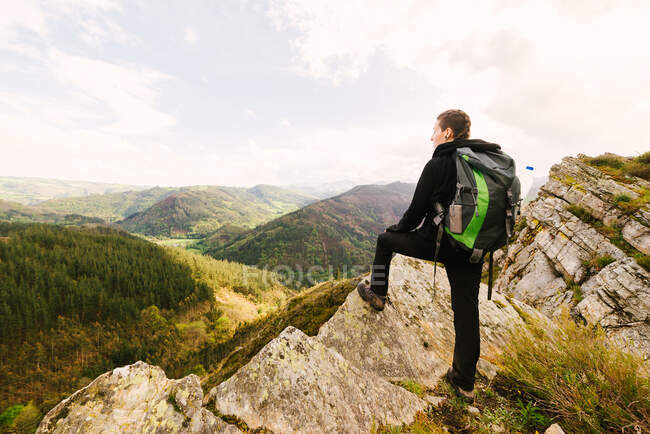 Back view of female hiker in trekking boots standing on rock and enjoying magnificent scenery of highlands in Hoces del Esva — Stock Photo