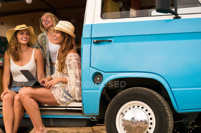 Обаятельная длинноволосая женщина в пляжной одежде, с улыбкой сидящая в автосалоне — стоковое фото