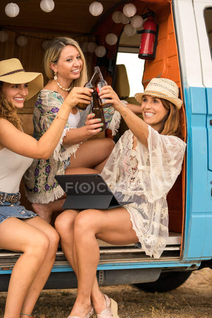 Amigos sorridentes batendo garrafas de cerveja comemorando férias — Fotografia de Stock