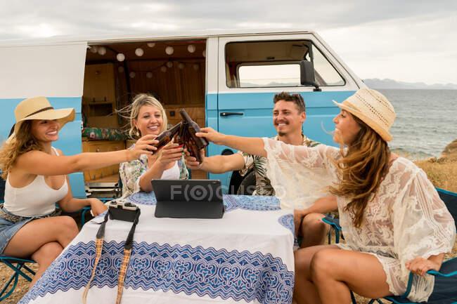 Amici sorridenti che chiudono bottiglie che celebrano la vacanza vicino auto in giorno lucente — Foto stock