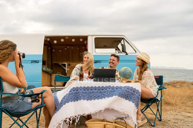 Весела подруга посміхається і тримає пляшку напоїв, сидячи за столом, а довга жінка фотографує сусідню блакитну машину. — стокове фото