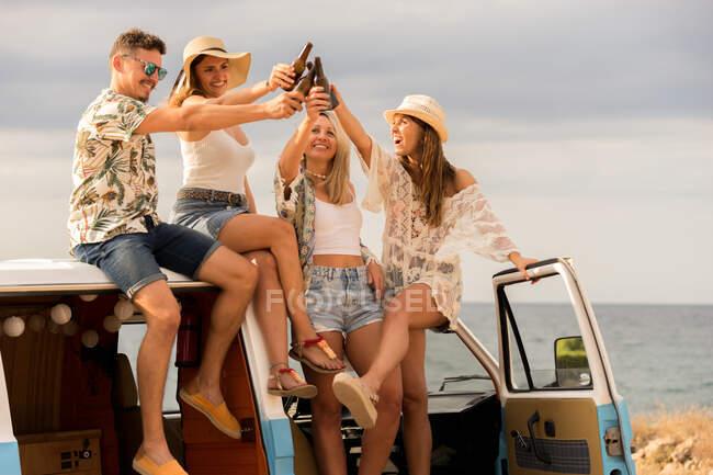 Des amis souriants cliquetis bouteilles célébrant des vacances sur le toit de la voiture dans la journée lumineuse — Photo de stock