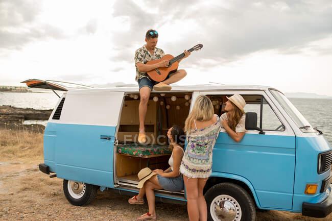 Чоловік грає на гітарі на даху автомобіля, а жінки із задоволенням слухають. — стокове фото