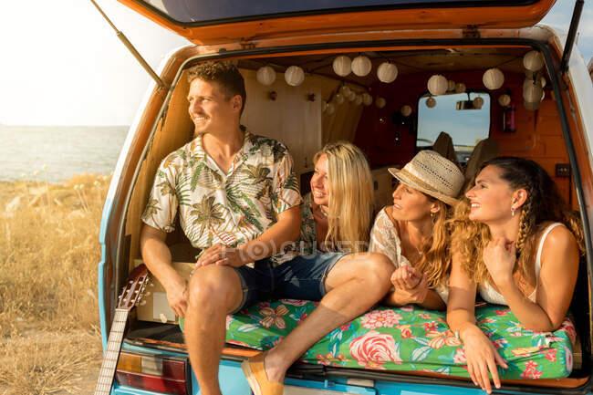 Amici rilassati confortevole collocazione sul bagagliaio di auto blu — Foto stock