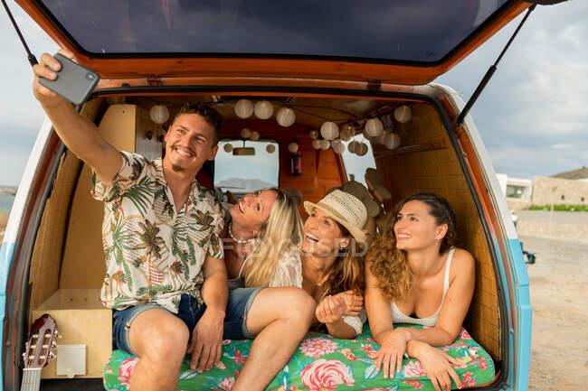 Приємна група молодих людей лежить на багажнику яскравого мінівену і в сонячний день розважається, користуючись мобільним телефоном на пляжі — стокове фото