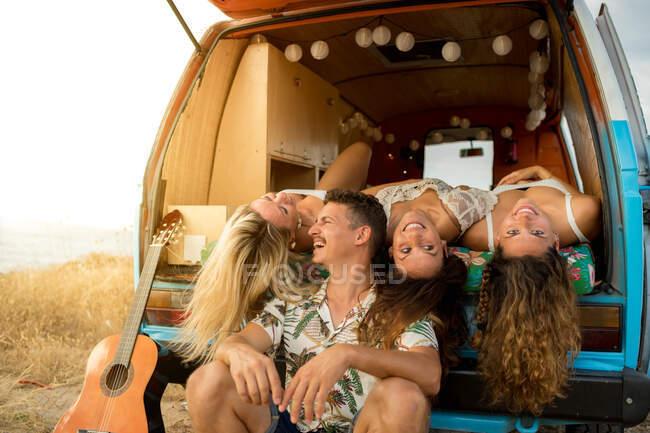 Приємні жінки, які лежать на багажнику яскравого мінівеня, висить голова і дивляться на камеру з стильним чоловіком у сонячному дні. — стокове фото