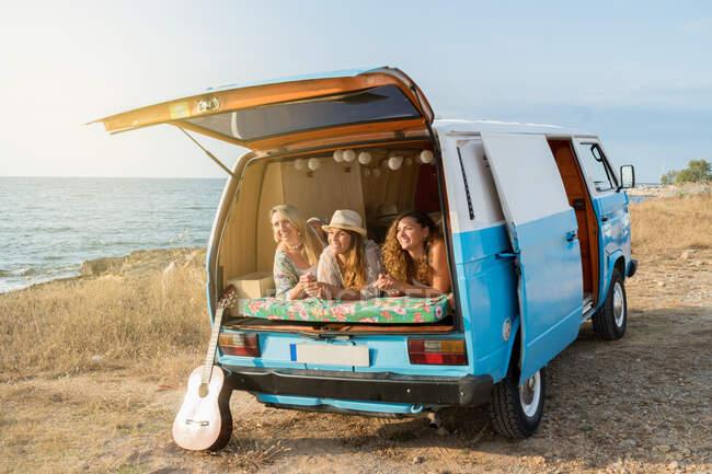 Joyeux dames agréables couché sur le tronc de minifourgonnette lumineuse avec guitare penché à proximité sur la plage par une journée ensoleillée — Photo de stock