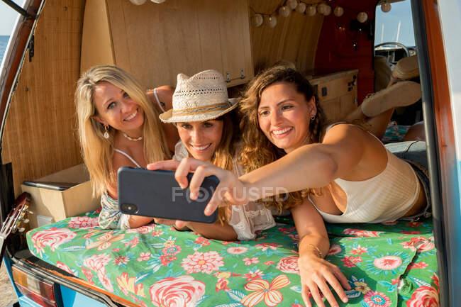 Веселі приємні пані лежали на багажнику яскравого мінівену і розважалися, користуючись мобільним телефоном на пляжі в сонячний день. — стокове фото
