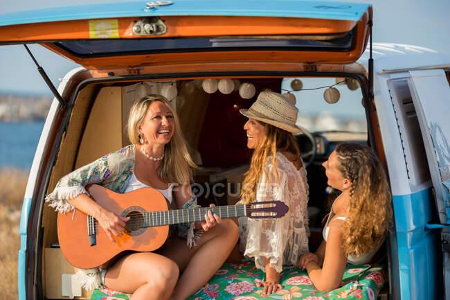 Веселих жінок з музичним інструментом, що відпочиває в машині під час подорожі. — стокове фото
