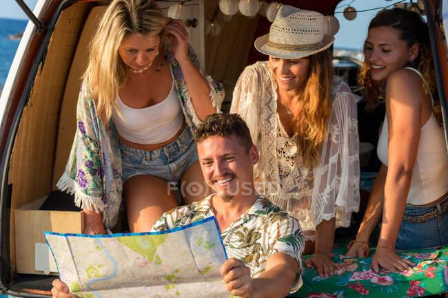 Homem curios ativo olhando para o mapa aberto estrada e encontrar rota com mulheres encantadoras em chapéu no tronco aberto do carro à beira-mar — Fotografia de Stock