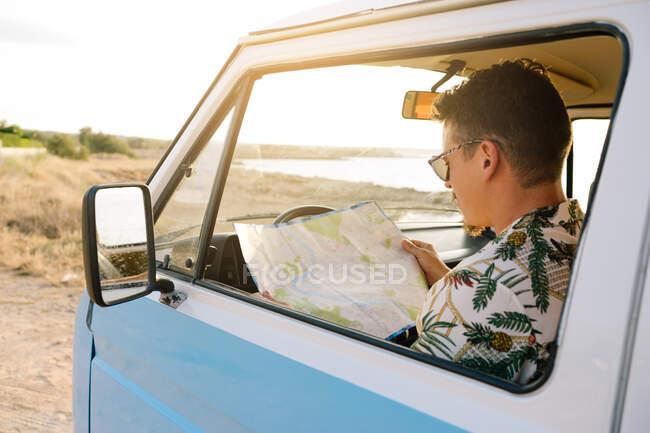 Hombre adulto planeando ruta para el viaje por carretera mientras está sentado en el coche en la orilla - foto de stock