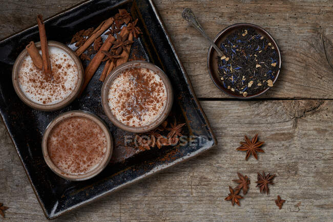 Top view of Masala chai served in ceramic bowls with star anise and cinnamon sticks arranged on wooden table with teapot and piece of cloth — Stock Photo