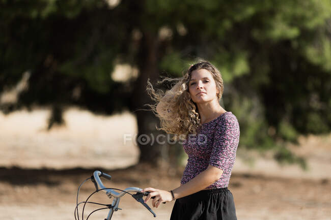 Calm female in summer outfit walking with bike in park on sunny day and looking away — Stock Photo