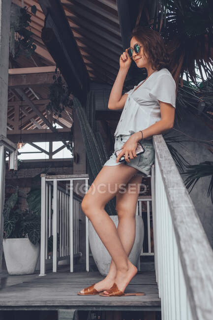 Low angle side view of happy slim female in gray casual shirt and shorts with smartphone touching sunglasses and looking away with interest while leaning on railing at wooden staircase in comfortable resort hotel on Bali — Stock Photo