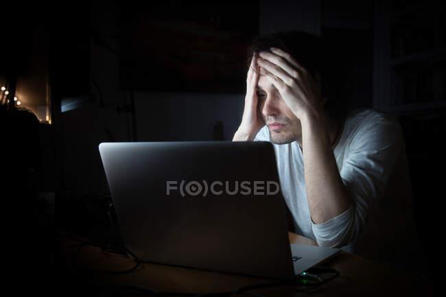 Hombre joven agotado en ropa casual sentado en la mesa con el ordenador portátil mientras trabaja hasta tarde en el proyecto remoto en la habitación oscura en casa - foto de stock