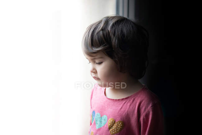 Side view of sad little girl standing near window and looking out while spending time at home — Stock Photo