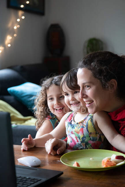 Cheerful young woman with cute little daughters sitting at table and enjoying video conversation with friends via laptop while spending evening at home — Stock Photo