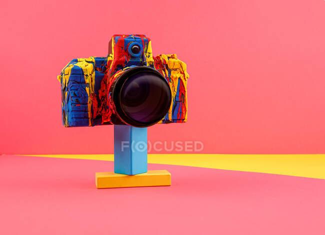 Фотокамера Creative retro розфарбована з різними кольорами на кольоровому фоні. — стокове фото