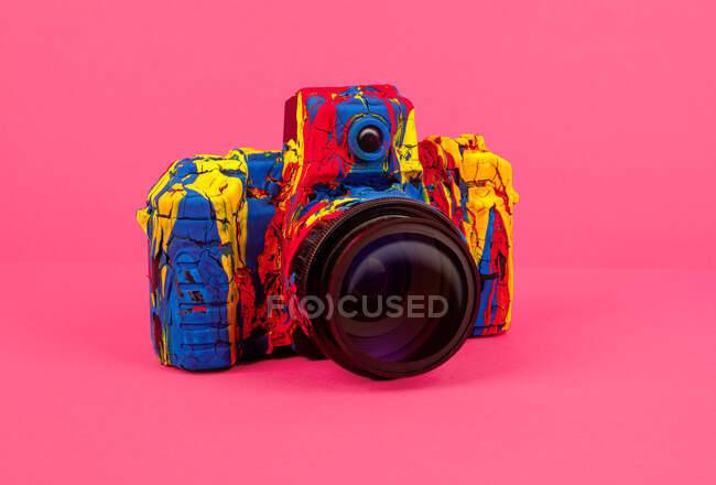 Творческая ретро-фотокамера, раскрашенная различными цветами на красочном фоне — стоковое фото