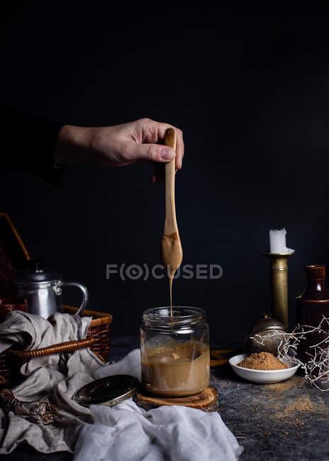 Невпізнавана жінка - кухар тримає чайник над прозорою скляною посудиною зі смачною карамеллю, яку кладуть на стіл у зв