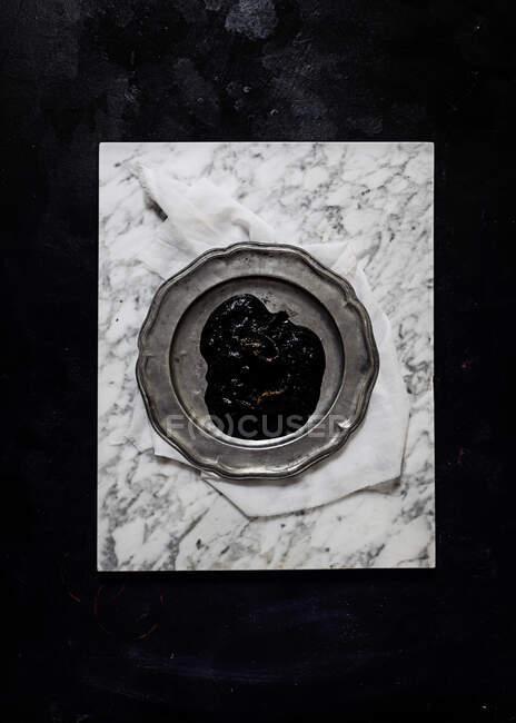 Vista superior de la placa de metal con gelatina de ciruela colocada sobre tela blanca sobre superficie de mármol sobre fondo negro - foto de stock