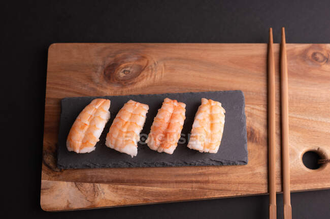 Top view of delicious sushi with rice and shrimps served on wooden board with chopsticks in restaurant — Stock Photo