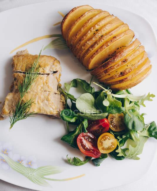 Vista superior de deliciosas batatas Hasselback assadas e salada de legumes frescos servidos com filé de frango assado decorado com raminho de endro — Fotografia de Stock