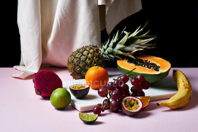Bodegón con frutas tropicales, papaya en rodajas, piña, pitaya y uvas en tabla de cortar de mármol - foto de stock