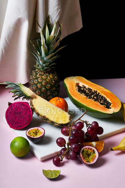 Still life with tropical fruits: sliced papaya, pineapple, pitaya and grapes on marble cutting board — Stock Photo
