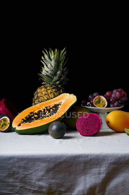 Still life with tropical fruits on white tablecloth and dark background — Stock Photo