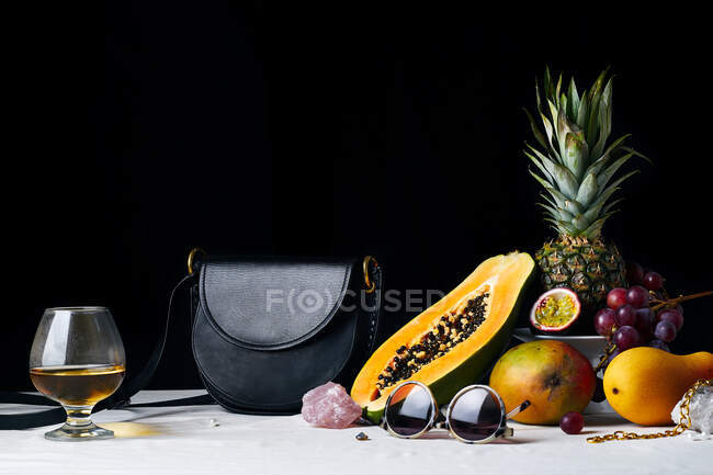 Still life with tropical fruits, gems, black leather bag and various objects — Stock Photo