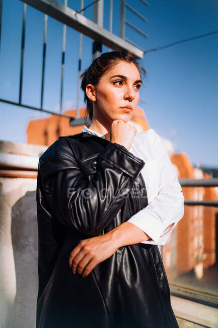 Serene female in trendy leather jacket standing on summer terrace looking away and enjoying sunny weather — Stock Photo