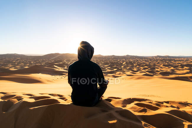 Back view of unrecognizable tourist sitting on sand dune and admiring majestic scenery of sunset in desert in Morocco — Stock Photo
