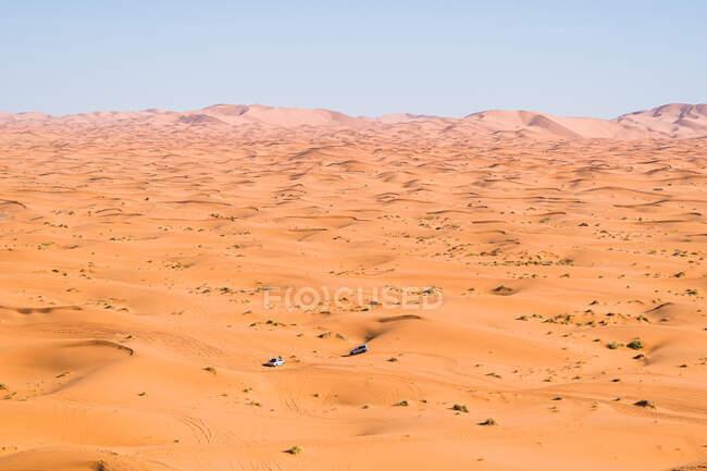Dall'alto pittoresca vista della guida in auto su dune di sabbia asciutta nel deserto nella giornata di sole in Marocco — Foto stock