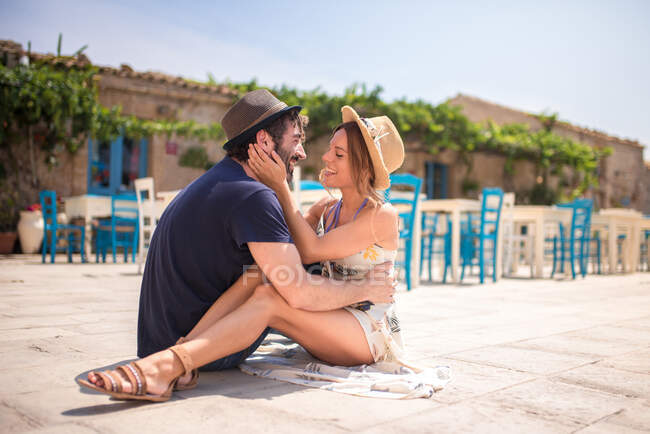 Smiling woman and unshaven man in hats and casual summer outfits looking at each other with love and embracing while sitting on floor on cafe terrace in hot sunny day — Stock Photo