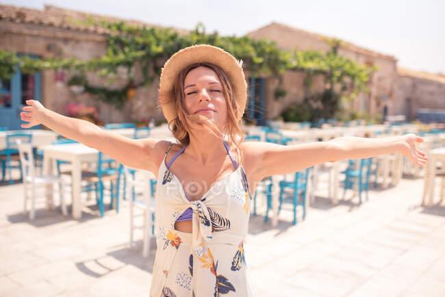Femme adulte séduisante en chapeau de paille portant une robe légère avec les yeux fermés et les bras ouverts tout en restant seule sur la terrasse du café contre les meubles bleus et blancs à la lumière du soleil — Photo de stock