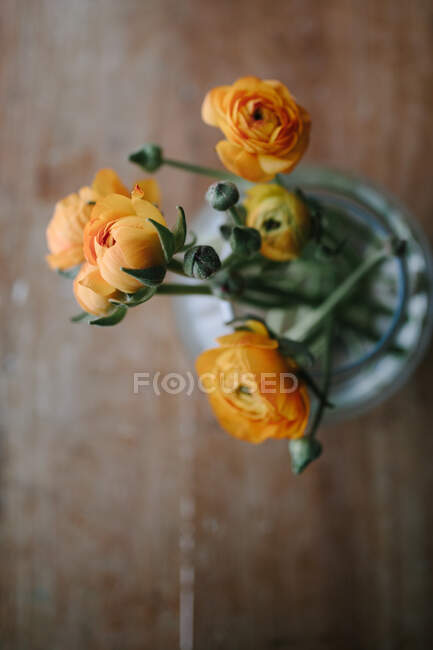 Top view of bunch of fresh orange peony flowers placed in clear glass jar on wooden table in rustic style — Stock Photo