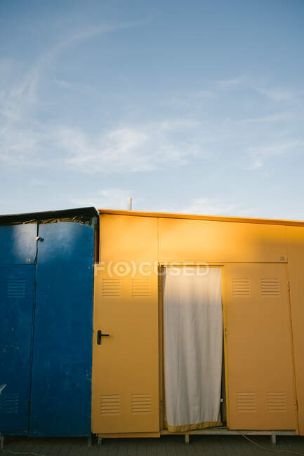 Shabby weathered yellow and blue metallic houses located on pavement in urban area during sunny summer day with clear blue sky — Stock Photo