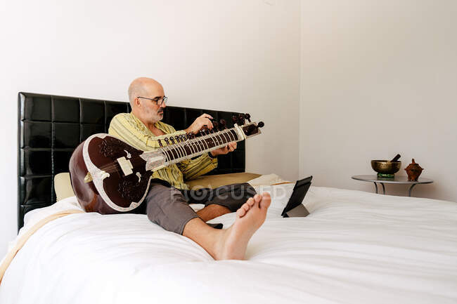 Elderly man sitting on bed with sitar and taking notes in notebook while watching online lesson on tablet — Stock Photo