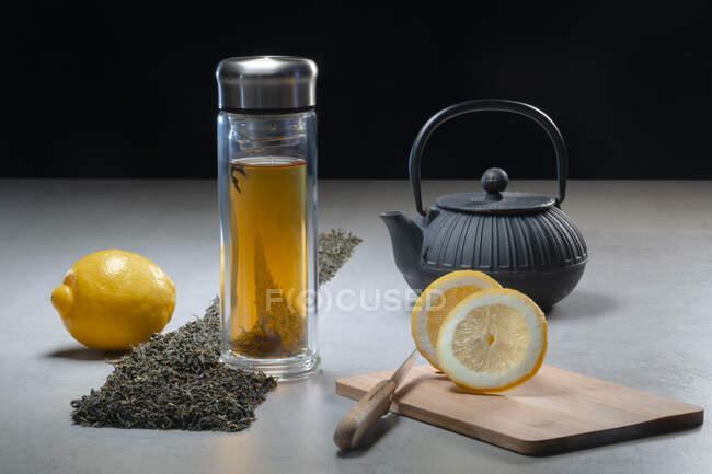 Boisson aromatique dans une tasse en verre et une théière disposées avec des citrons et des tas de feuilles de thé séchées sur la table sur fond noir — Photo de stock