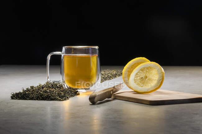 Boisson aromatique dans une tasse en verre arrangée avec des citrons et des tas de feuilles de thé séchées sur la table sur fond noir — Photo de stock