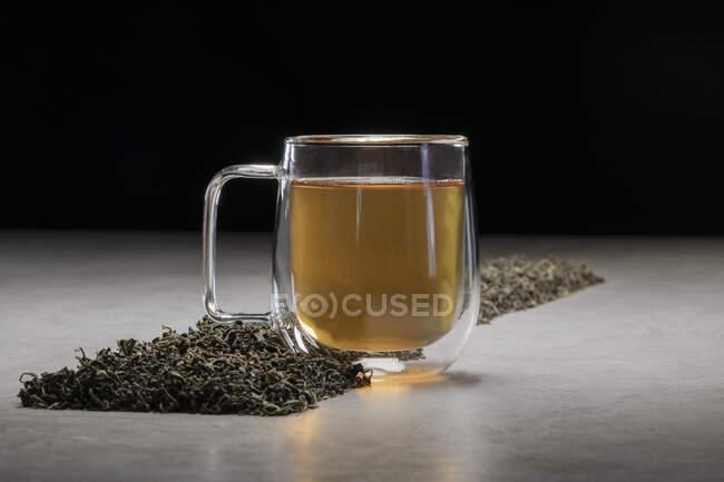 Boisson aromatique dans une tasse en verre disposée avec des tas de feuilles de thé séchées sur la table sur fond noir — Photo de stock