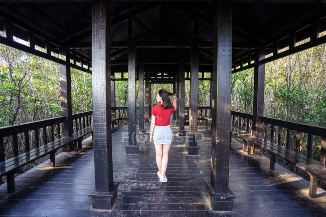 Back view of slim Asian lady in short skirt and red t shirt walking on antique wooden terrace with columns and benches surrounded by forest with green trees — Stock Photo