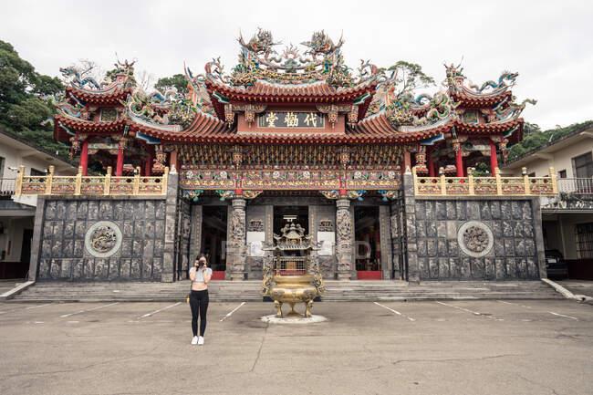 Жіночий турист у спортивному вбранні, який фотографує фотокамеру, стоячи біля фасаду буддійського храму у східному стилі, прикрашений скульптурами. — стокове фото